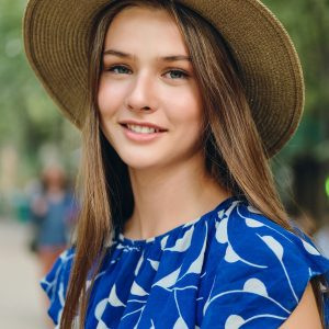 Portrait of pretty smiling girl in blue dress and hat dreamily looking in camera in city park